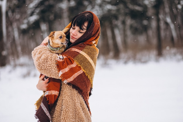 Jovem fora do parque com seu cachorrinho no inverno