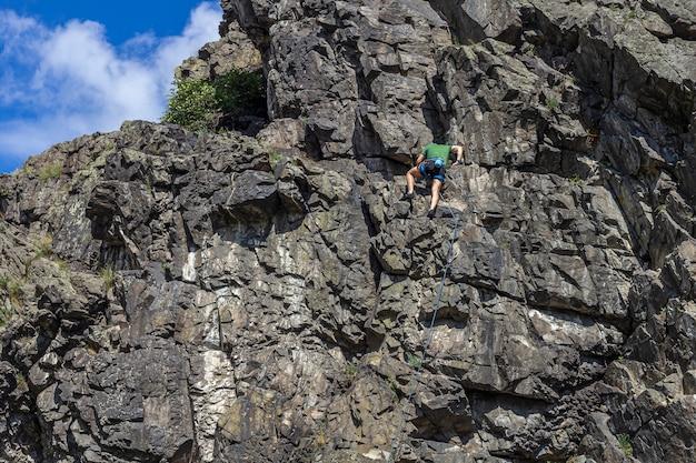 Jovem forte (alpinista) paira sobre uma parede de penhasco ou pedra. escalada, conceito de montanhismo.
