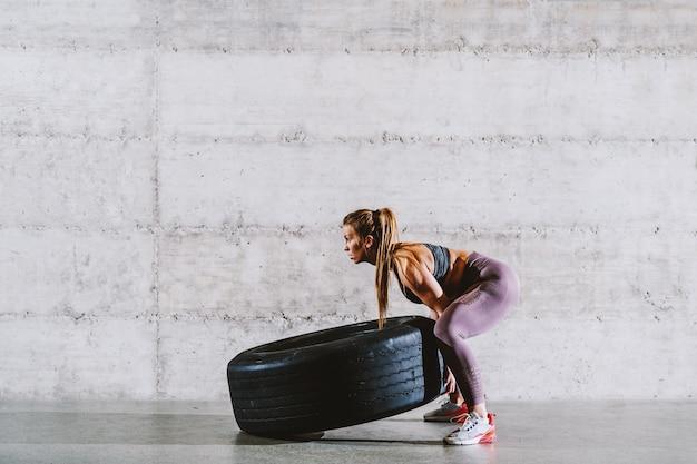 Jovem forte desportista caucasiana muscular em sportswear com rabo de cavalo lançando o pneu. conceito de estilo de vida saudável.