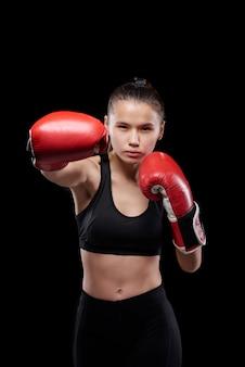 Jovem forte desportista com roupa desportiva e luvas de boxe a olhar para ti durante a luta contra um fundo preto