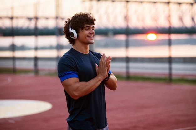 Jovem forte desportivo com fones de ouvido em pé no campo de treinamento e se preparando para o início da manhã malhar.
