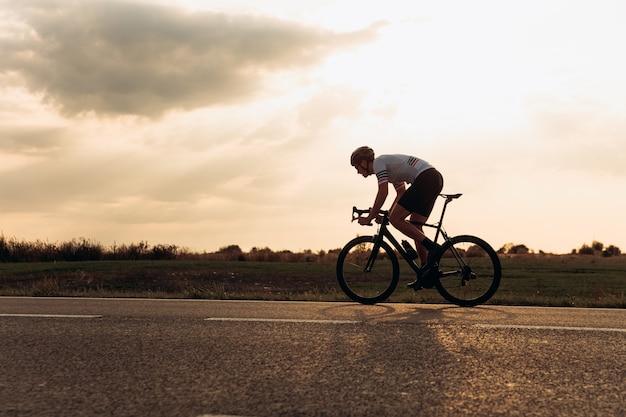 Jovem forte em roupas esportivas fazendo corridas de longa distância em bicicleta ao ar livre