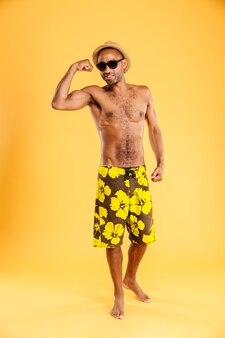 Jovem forte em trajes de banho mostrando os músculos sobre a parede laranja