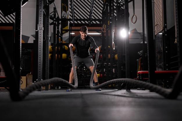 Jovem forte malhando com cordas de batalha no ginásio cross fit. desportista caucasiano musculoso fazendo excursão cruzada com cordas no ginásio de exercícios, fazendo treinamento físico sozinho