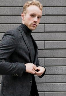 Jovem fotogênico fechando sua jaqueta