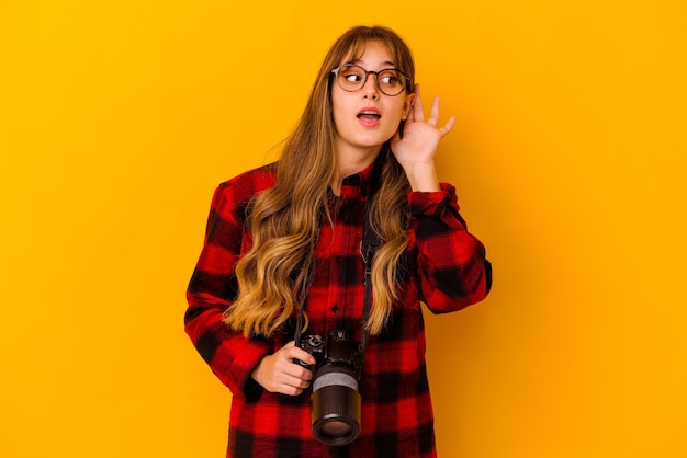 Jovem fotógrafa caucasiana isolada na parede amarela tentando ouvir uma fofoca