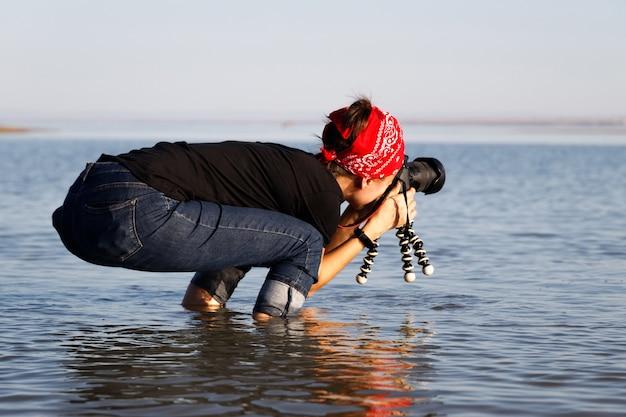 Jovem fotógrafa divertida com câmera profissional no mar