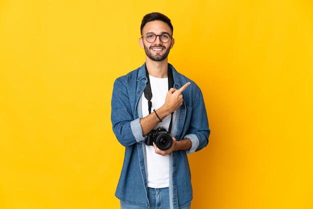 Jovem fotógrafa isolada na parede amarela apontando para o lado para apresentar um produto