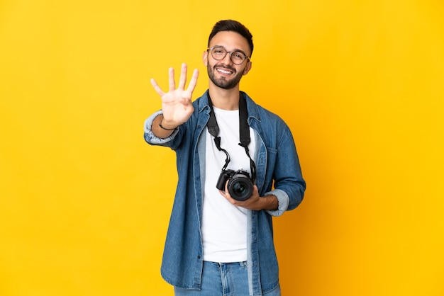 Jovem fotógrafa isolada na parede amarela feliz e contando quatro com os dedos