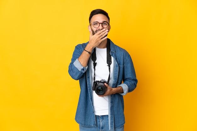 Jovem fotógrafa isolada na parede amarela feliz e sorridente, cobrindo a boca com a mão