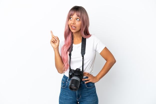 Jovem fotógrafa mulher de raça mista com cabelo rosa isolado em um fundo branco apontando uma ótima ideia