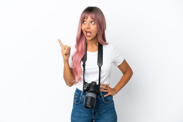 Jovem fotógrafa mulher de raça mista com cabelo rosa isolado no fundo branco com a intenção de descobrir a solução enquanto levanta um dedo
