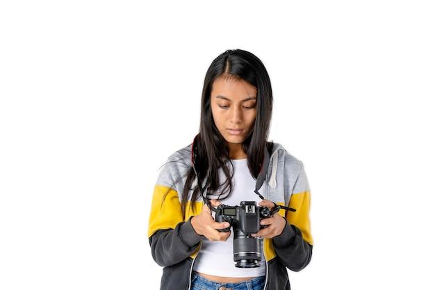 Jovem fotógrafa olhando para o visor da câmera para rever as fotos tiradas.