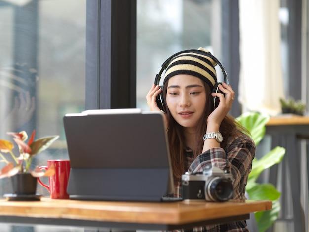 Jovem fotógrafa ouvindo música com fones de ouvido enquanto descansa do trabalho