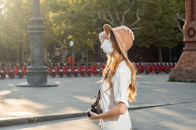 Jovem fotógrafa profissional viajando e tirando fotos com uma máscara facial ao ar livre.