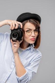 Jovem fotógrafa séria com a câmera concentrada em tirar fotos em pé isolado
