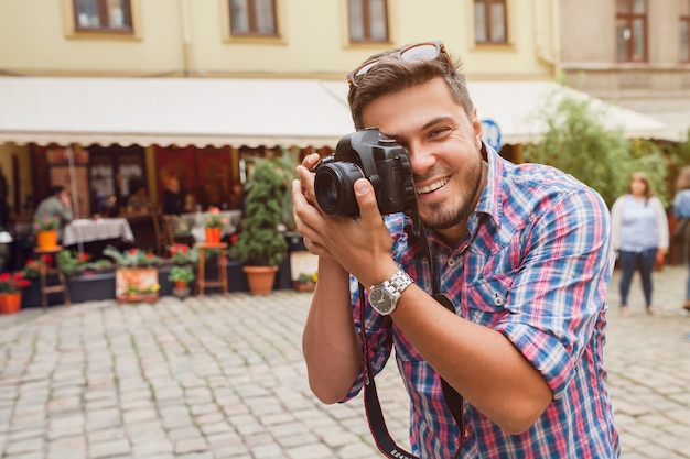 Jovem fotógrafa tirando fotos, tirando fotos com uma câmera digital para seus amigos