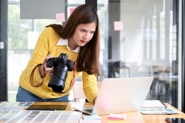 Jovem fotógrafa verificando imagens da câmera digital em seu laptop.