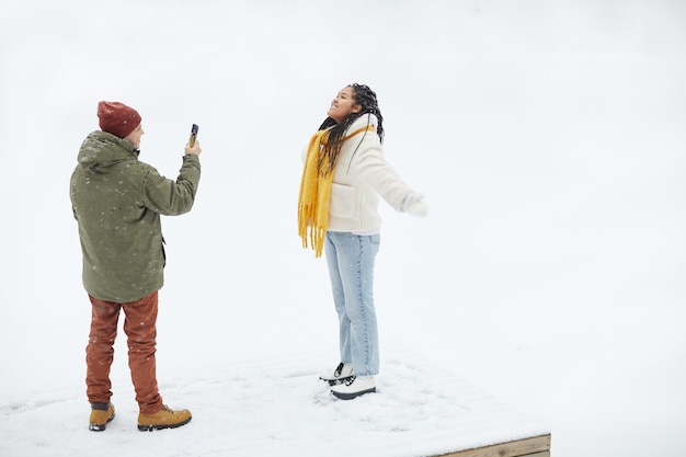 Jovem fotografando a namorada com o celular enquanto ela posa durante a neve