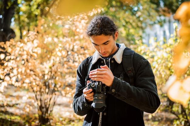 Jovem fotógrafo amador verificando fotos em sua câmera dslr moderna