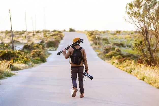 Jovem fotógrafo andando na estrada deserta com o tripé no ombro e câmera na mão