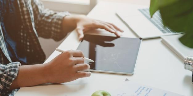 Jovem fotógrafo aplainar sua idéia sobre tablet no local de trabalho moderno