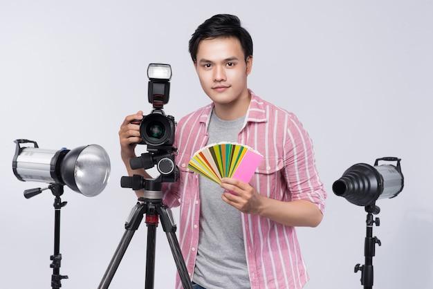Jovem fotógrafo asiático segurando uma câmera digital, enquanto trabalhava no estúdio