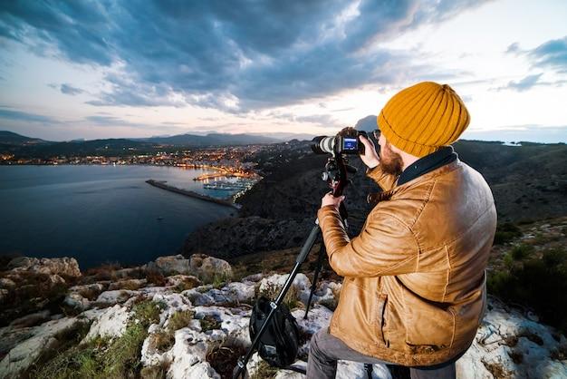 Jovem fotógrafo atraente fazendo fotos com a câmera no tripé ao pôr do sol