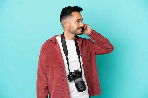 Jovem fotógrafo, caucasiano, isolado em um fundo azul, conversando com o celular.