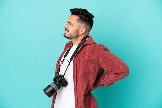 Jovem fotógrafo, caucasiano, isolado em um fundo azul, sofrendo de dor nas costas por ter feito um esforço