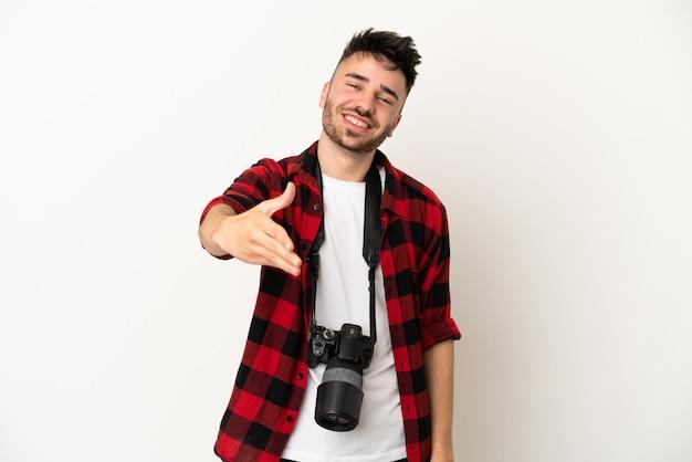 Jovem fotógrafo, caucasiano, isolado no fundo branco, apertando as mãos para fechar um bom negócio