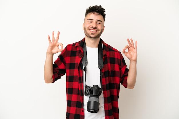 Jovem fotógrafo, caucasiano, isolado no fundo branco, mostrando um sinal de ok com os dedos