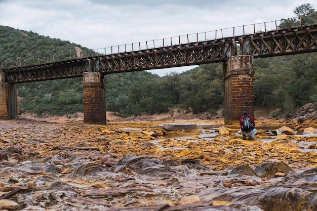 Jovem fotógrafo com mochila e boné fotografando uma velha ponte de ferro sobre o rio tinto