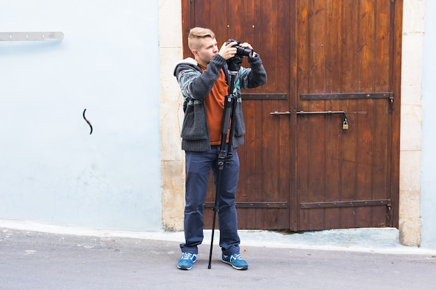 Jovem fotógrafo com um monopé fazendo fotos na cidade.