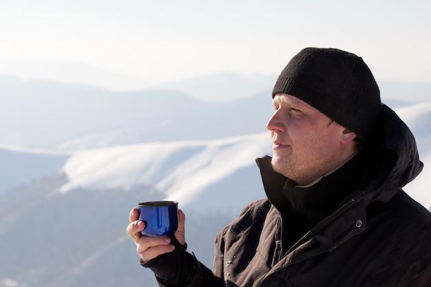 Jovem fotógrafo de homem sorridente em roupas de inverno, bebendo chá de garrafa térmica