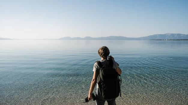 Jovem fotógrafo de pé à beira-mar, segurando a câmera e tripé