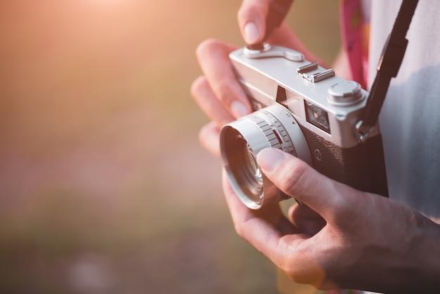 Jovem fotógrafo do homem viajante com mochila, tirando foto com sua câmera de filme retrô