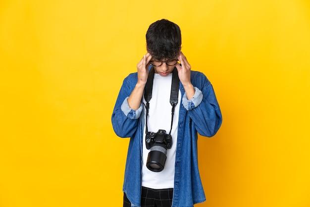 Jovem fotógrafo em uma parede amarela isolada com uma expressão cansada e doente