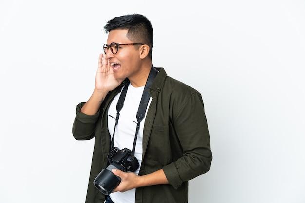 Jovem fotógrafo equatoriano isolado no fundo branco gritando com a boca bem aberta para o lado