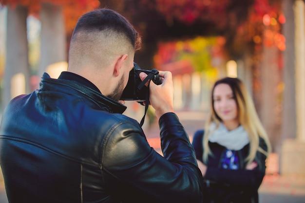 Jovem fotógrafo fazendo uma foto de uma linda garota em um parque