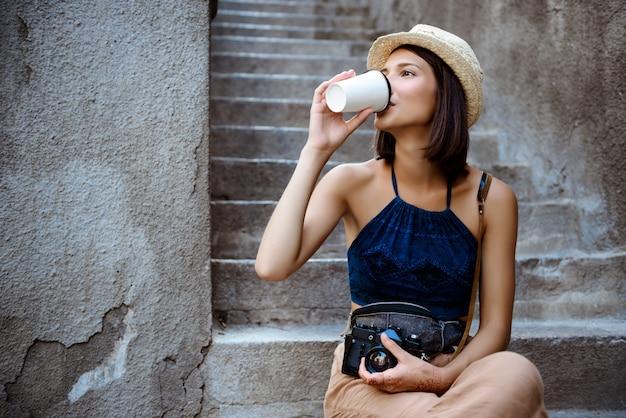 Jovem fotógrafo feminino morena linda bebendo café, sentado na escada.