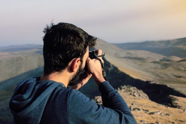 Jovem fotógrafo fotografa o pôr do sol nas montanhas