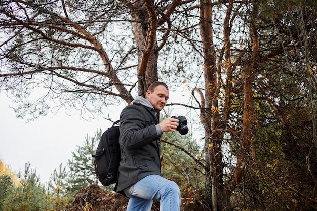Jovem fotógrafo fotografando na floresta de outono