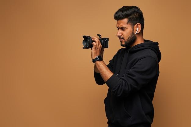 Jovem fotógrafo hindu com capuz preto e câmera na parede