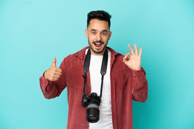 Jovem fotógrafo homem caucasiano isolado em fundo azul, mostrando sinal de ok e gesto de polegar para cima