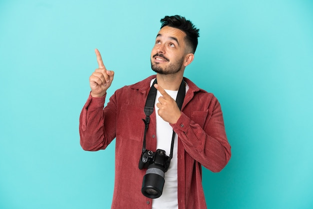 Jovem fotógrafo homem caucasiano isolado em um fundo azul apontando com o dedo indicador uma ótima ideia