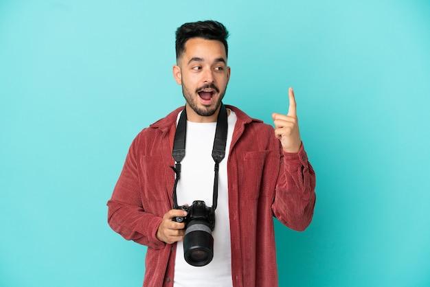 Jovem fotógrafo homem caucasiano isolado em um fundo azul com a intenção de descobrir a solução enquanto levanta um dedo