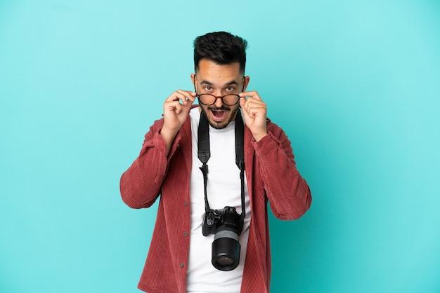 Jovem fotógrafo homem caucasiano isolado em um fundo azul com óculos e surpreso