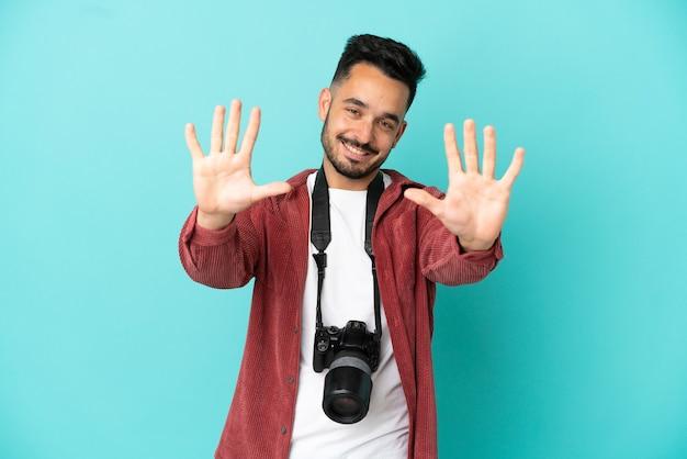 Jovem fotógrafo homem caucasiano isolado em um fundo azul, contando dez com os dedos