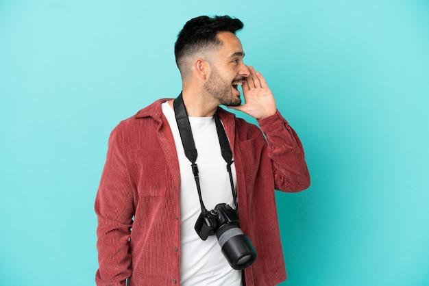 Jovem fotógrafo homem caucasiano isolado em um fundo azul gritando com a boca bem aberta para a lateral